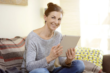 Woman at home working on sofa with a tablet PC or surfing the web