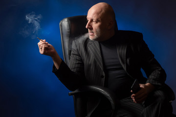 Businessman. Bald man in a black business suit. A man smokes a cigarette while sitting in a chair. Thoughtful man is looking forward. Smoke break.