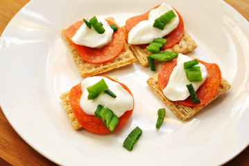 Appetizer of Wheat Crackers, Pepperoni, Sour Cream & Sliced Scallions