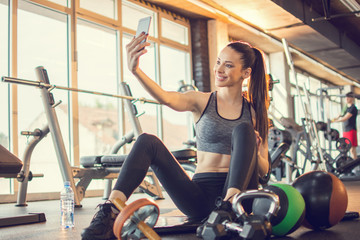 Beautiful girl in activewear using smart-phone to take a selfie photography during exercise break in gym