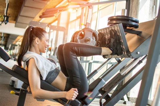 Side view of fit young sportswoman flexing her leg's muscles on exercise machine at the gym during morning workout