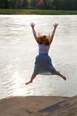 Jugendliche am Fluss springt in die Höhe