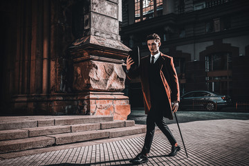 Fashion portrait of young man on red coat, white shirt, black suit and cane walking on streets of city background. Model shooting Wall mural