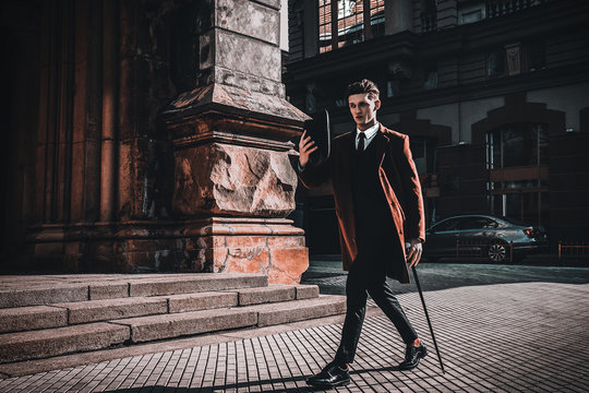Fashion portrait of young man on red coat, white shirt, black suit and cane walking on streets of city background. Model shooting