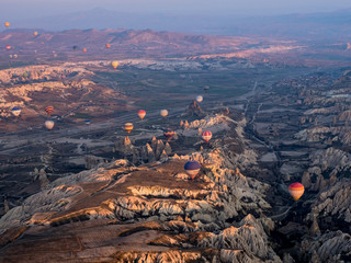 Colorful hot air balloons above Turkish National Park in Goreme. Panorama of Cappadocia landscape - multi colored balloons flying over mountain valley of ancient cave town Uchisar. March, 2019