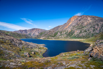 Hiking in the arctic - the Arctic Circle Trail (ACT) along a crystalline lake during summer in Greenland with beautiful landscape views, grass, mountains, blue sky