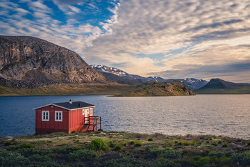 Red house (hut) on the lake surrounded by mountains in arctic Greenland during sunset