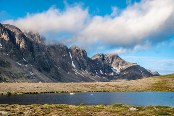 Hiking along steep mountain slopes on arctic Greenland near Sisimiut on the Arctic Circle Trail (ACT) with lake and running clouds