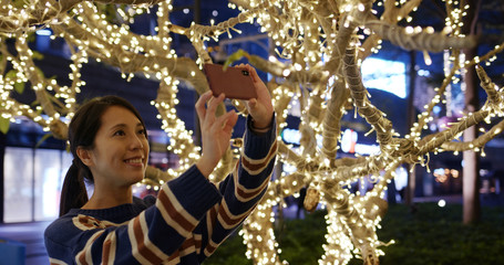 Woman take photo with cellphone of Christmas night