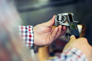Technician in a Metal Manufacturing Company Measuring with Digital Vernier Caliper