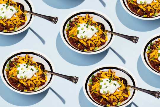 Pattern of bowls of chili with cheese, chives and sour cream