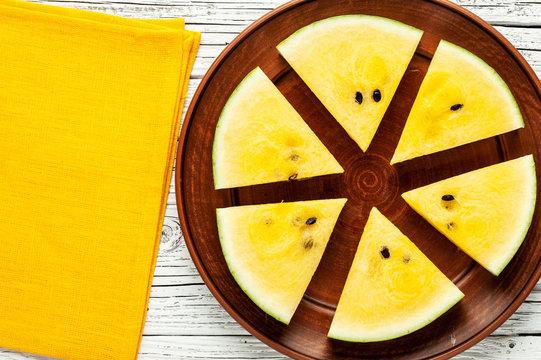 yellow watermelon on white wood.