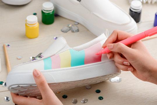 Girl painting white slip-on shoes