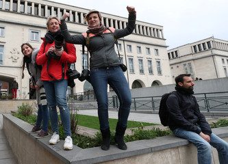 Female photo journalists look on while covering a rally on the International Women's Day in central Brussels