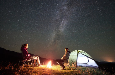Happy couple tourists resting at summer night camping in the mountains. Smiling man and woman sitting on chairs beside campfire and illuminated tent under starry sky full of stars and Milky way.