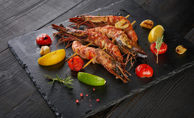 Barbeque grilled prawns with spicy ingredients garlic and tomato on dark wooden table