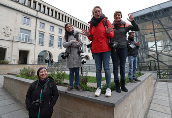 Belgian female photo journalists look on while covering a rally on the International Women's Day in central Brussels