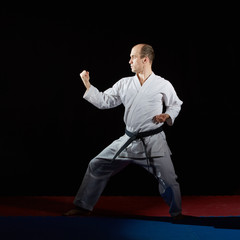 On red and blue tatami active athlete performs formal karate exercises on red and blue tatami
