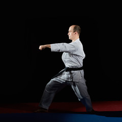 On the red and blue tatami in karategi athlete doing formal exercises karate