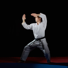 On the red and blue tatami in karategi athlete trains formal exercises karate