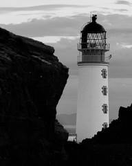 Close up of Rua Reidh lighthouse along cliff in Scotland, in black and white.