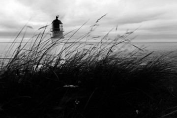 Top of Rua Reidh lighthouse with moving grass in the foreground and sea in the background, in black and white.