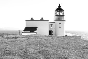 Small Stoer Head lighthouse with keepers house and bright sea in the background, in black and white.