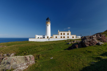 Rua Reidh Lighthouse with keepers house and walls on grassy hillside along the coast. Rocks in the foreground and blue sky.