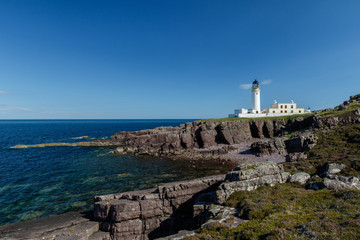 Rua Reidh Lighthouse with keepers house on a rocky coastline with blue sky.