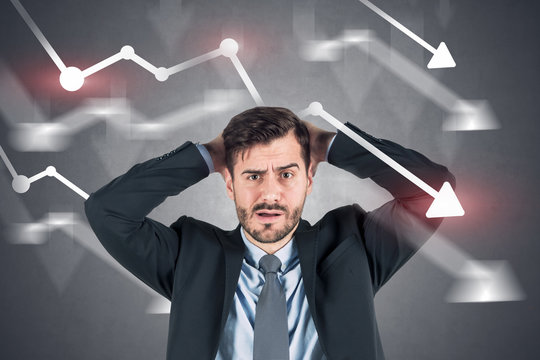 Confused businessman, falling graphs