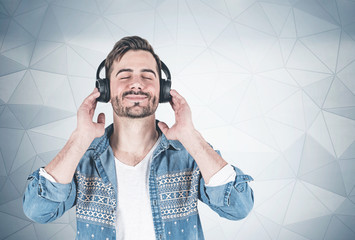 Smiling man listening to music, wall