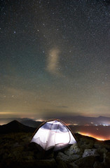 Tourist camp at summer night on the top of rocky mountain. Illuminated tent under beautiful night sky full of stars. On background starry sky, mountains and luminous towns. Tourism adventure concept