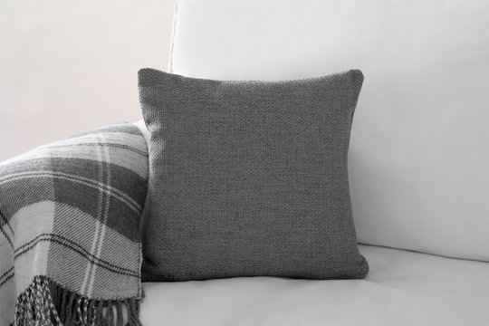 Mockup of a grey square cushion on a white sofa next to a grey plaid blanket.