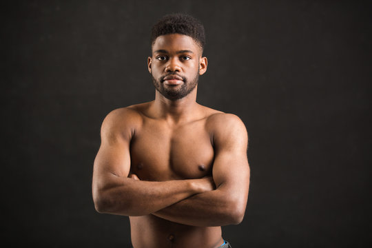 handsome african man with muscles on black background
