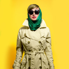 Young elegant woman in trendy coat wearing scarf and sunlgasses over bright yellow background