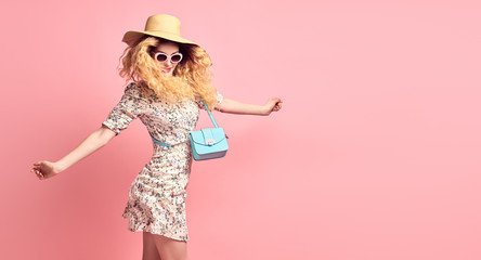 Fashion. Inspired Young woman laughing dance in Studio. Lovable joyful Girl Having Fun, Wavy Hairstyle, Stylish fashionable dress, handbag, summer hat. Positive emotion, happy face expression