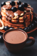 Poster Chocolate Hot chocolate drink in a cup and pancakes with banana, chocolate sauce and grapes in plate, on dark background
