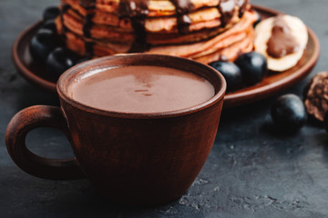 Hot chocolate drink in a cup and pancakes with banana, chocolate sauce and grapes in plate, on dark background