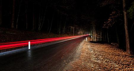 Lichtstreifen auf Waldweg im dunkeln. Waldstraße mit rotem Lichtstreifen bei Nacht. Forest road with red light trails at night.