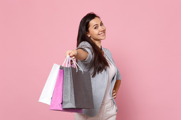 Portrait of smiling young woman in striped jacket holding package bag with purchases after shopping isolated on pink pastel background. People sincere emotions, lifestyle concept. Mock up copy space.