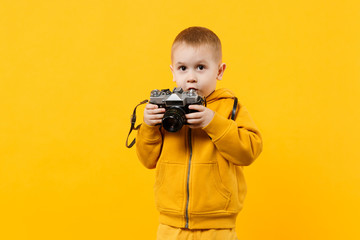 Little kid boy 3-4 years old wearing yellow clothes hold camera isolated on orange wall background, children studio portrait. People sincere emotions, childhood lifestyle concept. Mock up copy space.