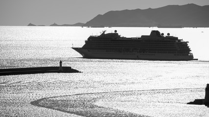 Cruise ship leaving the harbor in back light with black and white filter.
