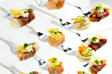 Background of mixed canapes on metal forks. White background.