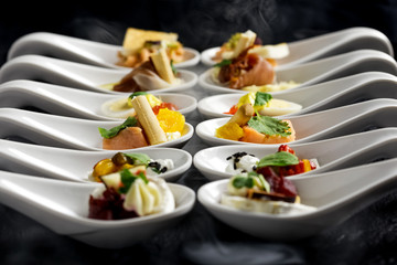 Two rows of canapes on white ceramic spoons. Black background with smoke.