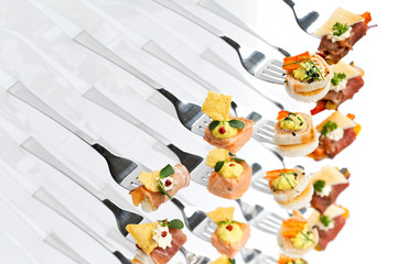 Mixed canapes on metal forks. White background.
