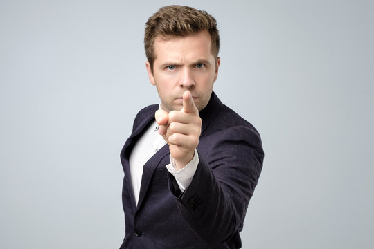 Young business man pointing with finger to the camera and to you