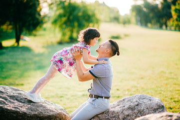 Dad and daughter summer outdoor activity. Loving father adore his lovely playful cheerful baby. Parent and child have fun in park. Little girl falling down at father. Happy family lifestyle portrait.