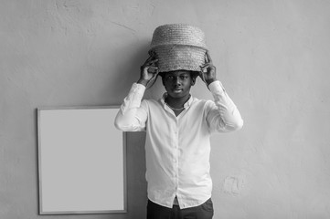 Closeup lifestyle portrait of strange young african black man holding straw basket above his head on textured wall background and looking at camera. Dark-skinned nigerian boy  indoor funny portrait.