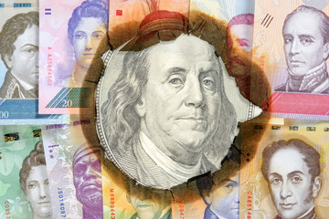 Concept of hyperinflation Venezuela. Burned Venezuelan money with the image of statesmen, through hole in which you can see an unburned one hundred dollar bill with Franklin. Close up.
