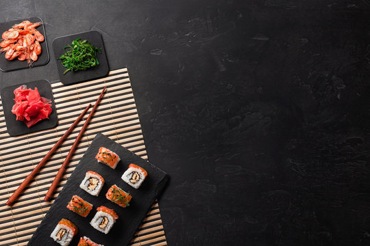Set of sushi and maki with a bottle of wine on stone table. Top view with copy space